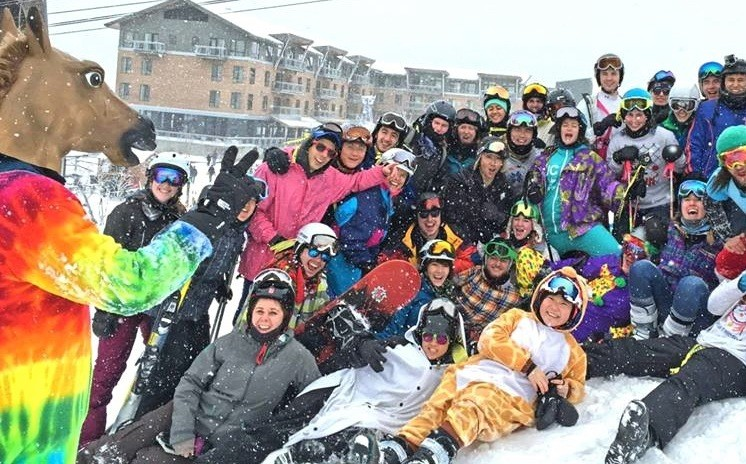 Members of Columbia's Ski and Snowboard Club, all wearing colorful gear, pose in the snow.